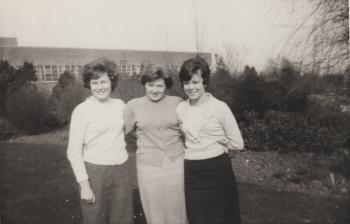 Julie Moore with 2 friends in Brtish Nylon Spinners  factory grounds; buses in background, that were free to staff