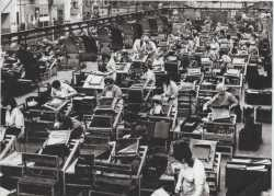 Factory floor at Morris Motors, showing the assembling of copper brass radiators; c. 1970. Carol Price is in the second row, wearing spectacles.