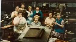 A leaving do for a factory worker at Morris Motors c. 1980s. In front of the group we see a jig - the copper brass was placed within the jig to assemble the radiator.
